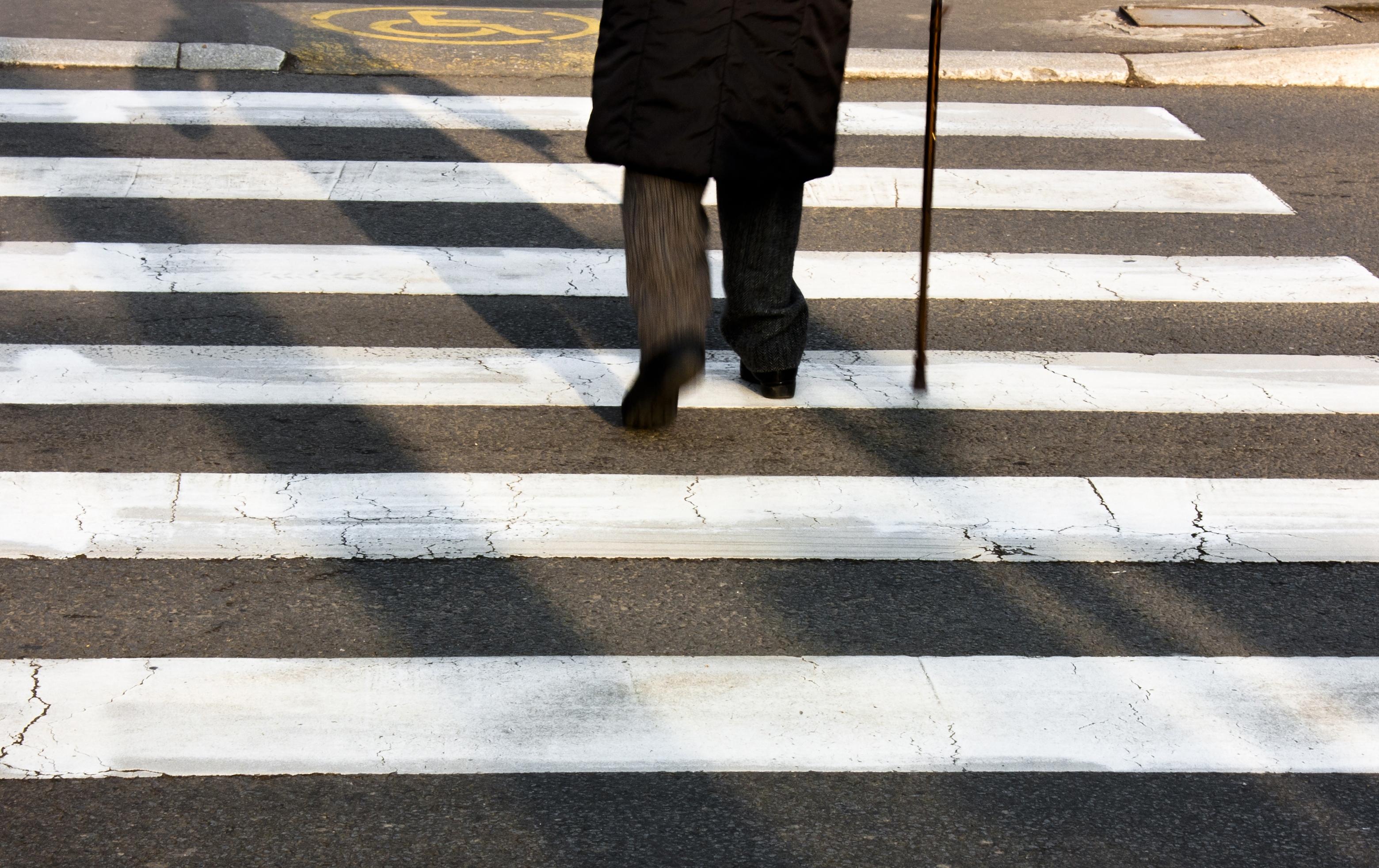 Older gentleman crosses the street using a cane
