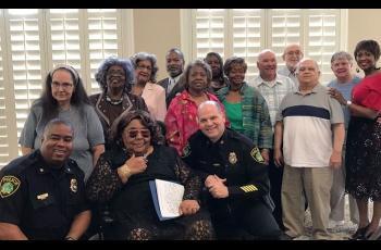 Police officers posing for a picture with older adults