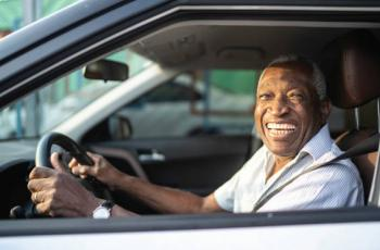 Older man driving and smiling