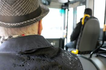 Older man sitting on the bus with rain on his coat