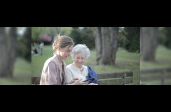 Young woman sitting on a bench with an older woman, looking at a digital reading device.