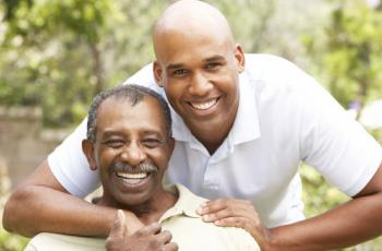 Young African American man embracing older man.