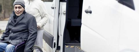 Older gentleman exits van with assistance from specialized chair