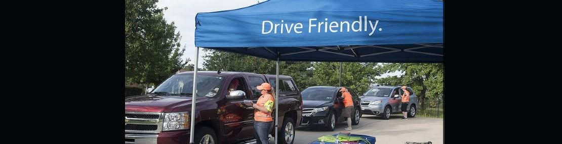 """Three cars in line for a CarFit screening by an expert with a blue tent reading: """"Drive friendly."""""""