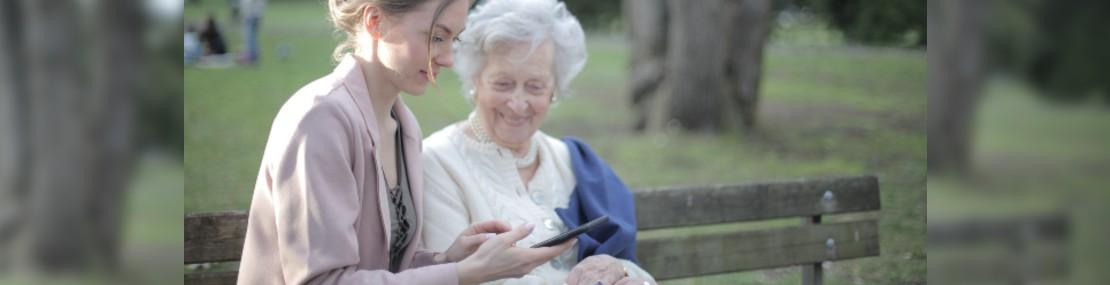 Young woman sitting with an older woman on a park bench. Both are looking at a digital reading device.