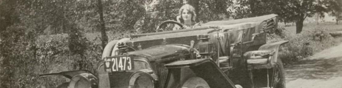 Florence Lawrence in the driver's seat of a car.