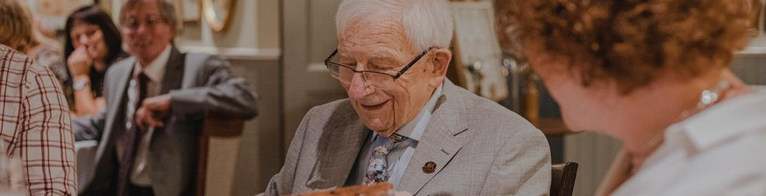 Senior man looking down at a gift, smiling at a table with others