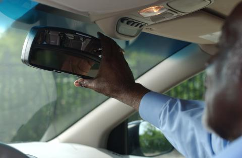 Older adult driver adjusts rearview mirror
