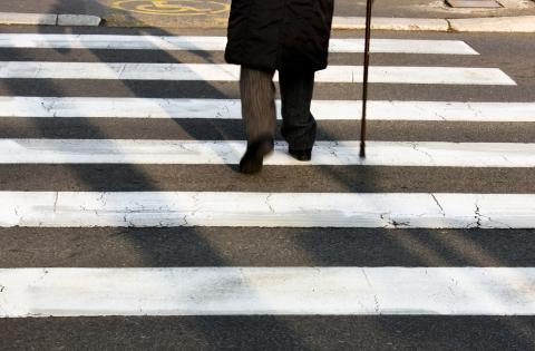 Older gentleman crosses the street using a cane