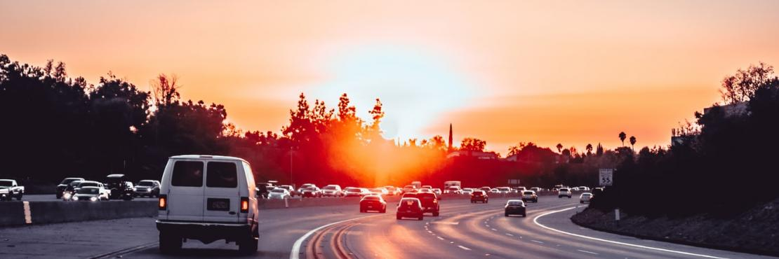 White van on divided freeway with safety features at sunset